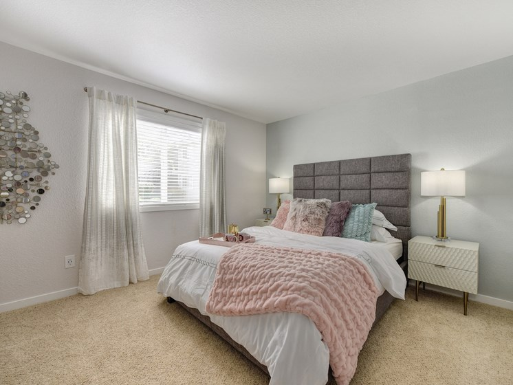 Bedroom with Carpet, Gray Head Board, White Bedside Dresser and Lamp