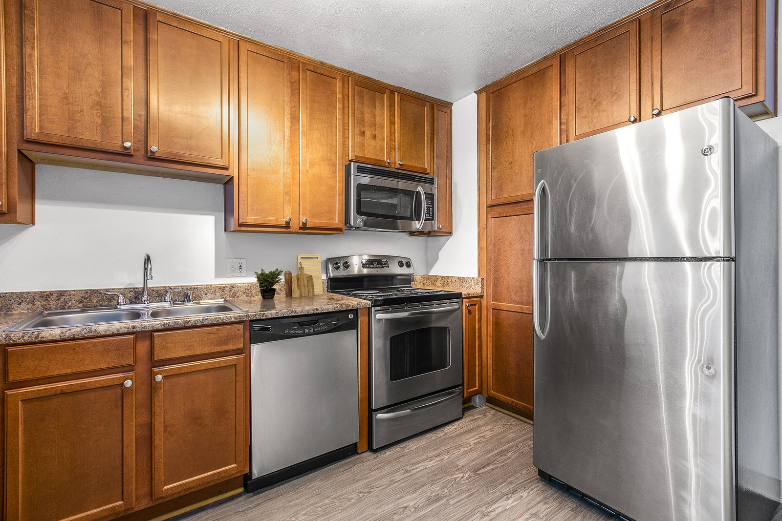 Apartments for Rent in Torrance, CA - Milano Kitchen with Stainless Steel Appliances, Wood Cabinets, and Granite Countertops