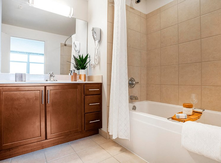 Alta's apartment bathrooms feature wood cabinets and marble countertops
