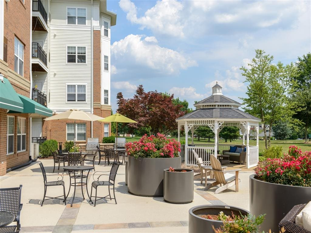 Large Resort-Style Furnished Outdoor Patio With Comfortable Amenities, Lavish Landscaping And Open Fields
