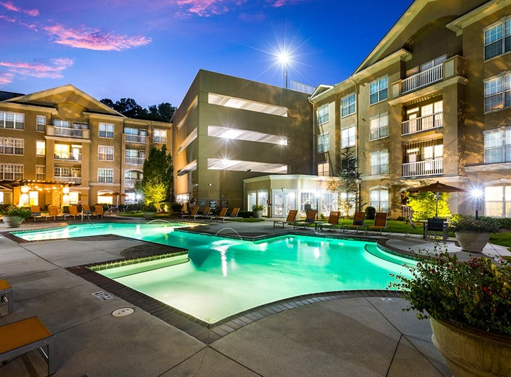 The Savoy's lighted pool and parking garage at twilight