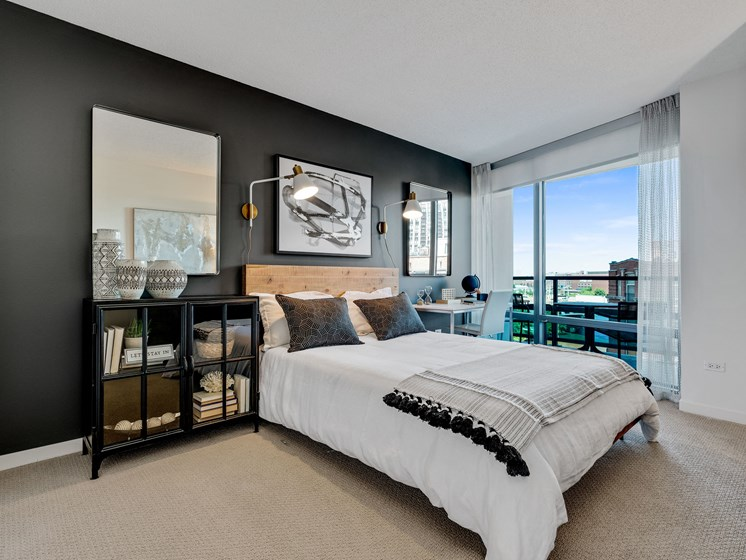 Bedroom layout with queen bed, floor to ceiling window, black accent wall, and modern/eclectic furniture