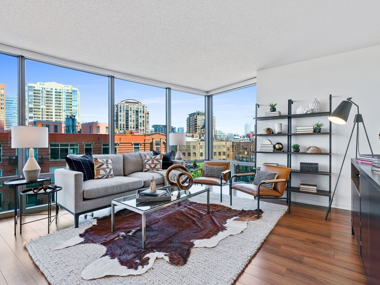 Living room picture with glass coffee table, two rugs, over wood flooring, with a couch shelving, and floor to ceiling windows