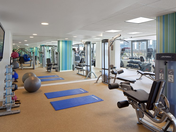 Fitness center with yoga mats, strength training, and cardio equipment