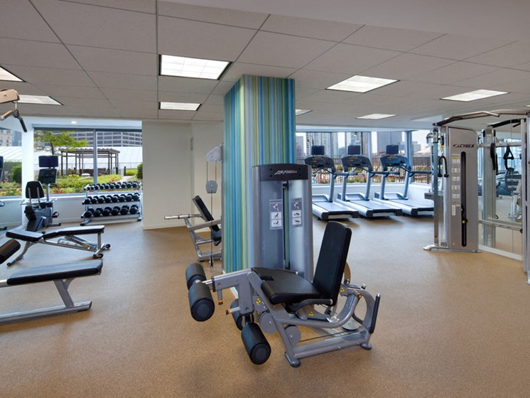 Fitness center with weight training and cardio machines in background
