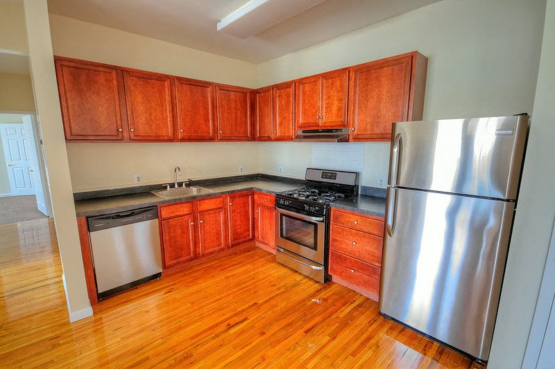 Kitchen with stainless steel appliances, wooden cabinets and hardwood floors
