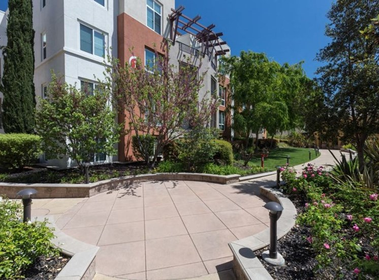 walkway outside apartment building surrounded by greenery