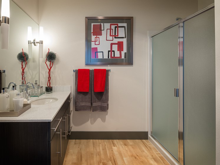 ArtHouse Downtown Seattle Apartments - Bathroom With Sleek Black Cabinets, Chic Red Decor and Modern Fixtures