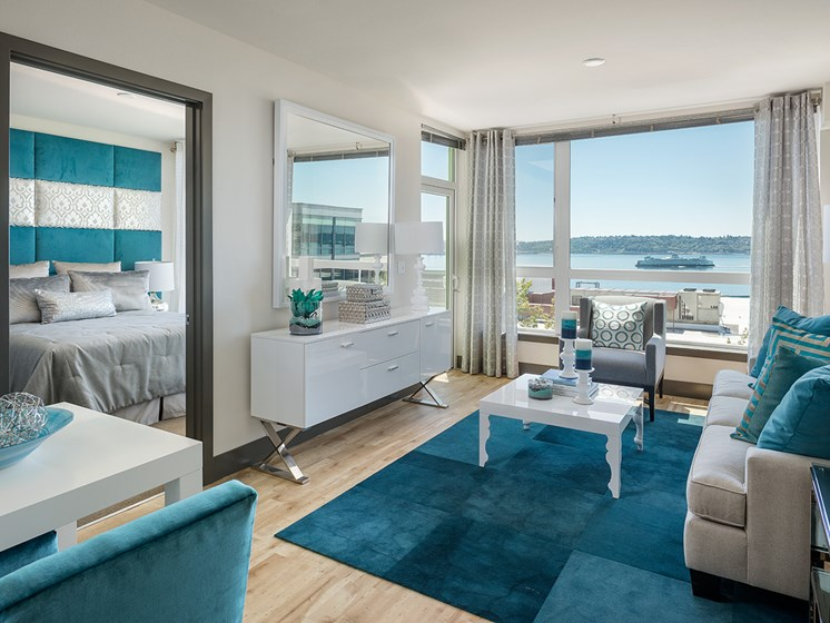 ArtHouse Apartments for Rent in Downtown Seattle - Living Room With Hardwood Style Flooring, Large Window With Ocean Views and Cozy Blue Decor