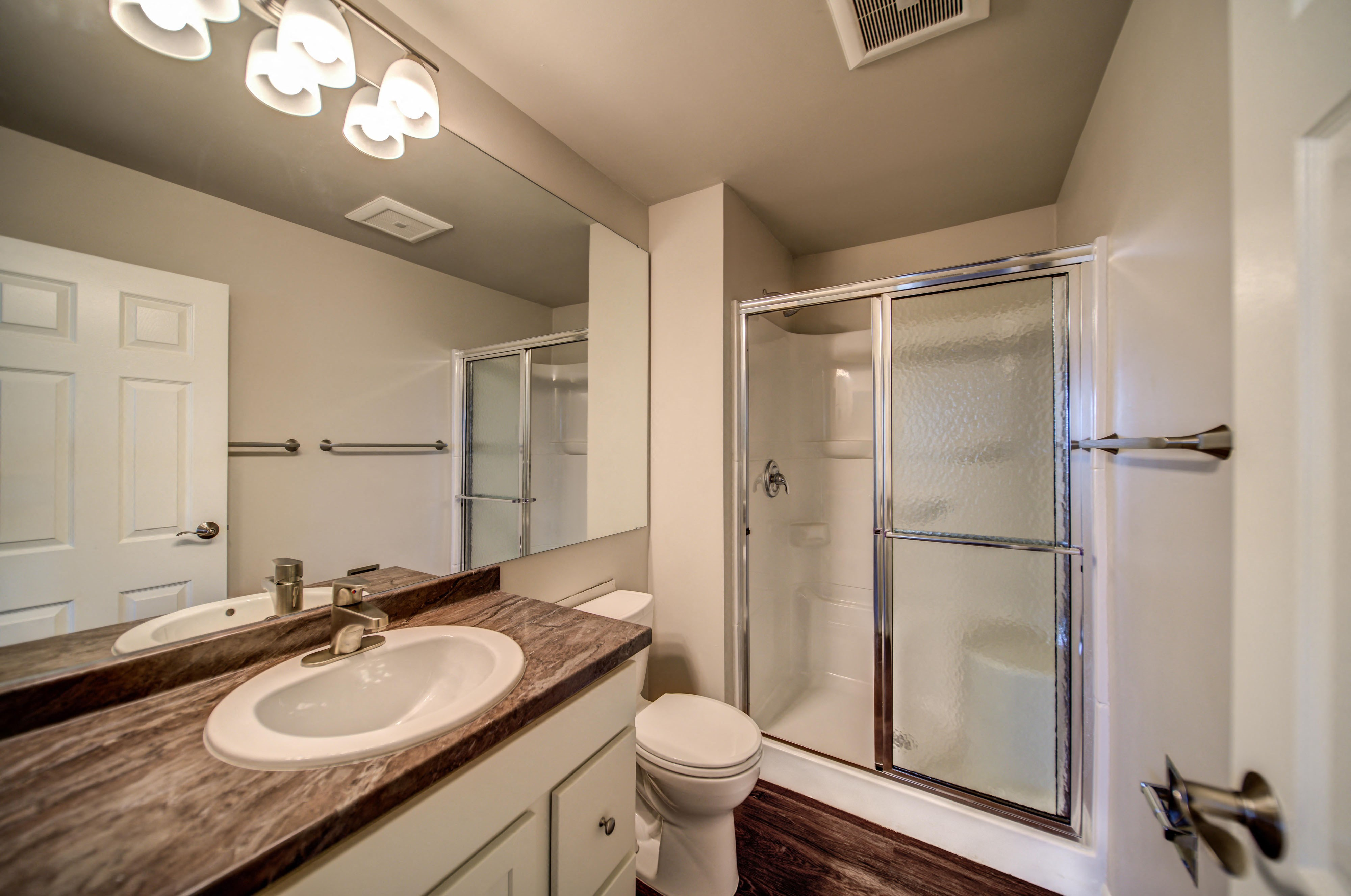 Sliding Glass Shower in Bathroom with White Cabinets