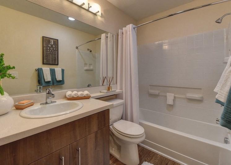 Bathroom with Wood Inspired Floor, Toilet, Vanity, and Bathtub