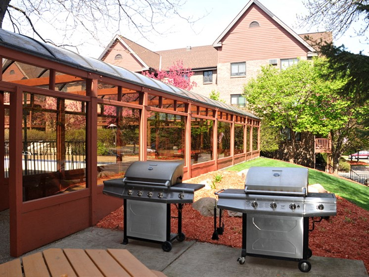 Two silver grills next to shaded terrace