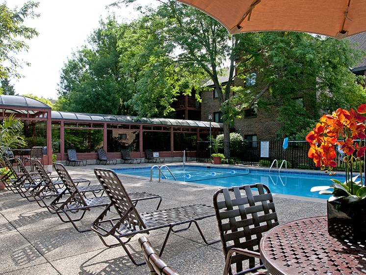 Outdoor pool with lounge chairs, umbrella tables, and shaded areas