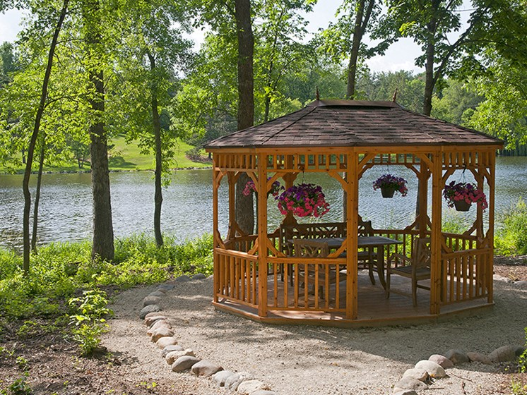 wooden gazebo surrounded by trees overlooking a lake