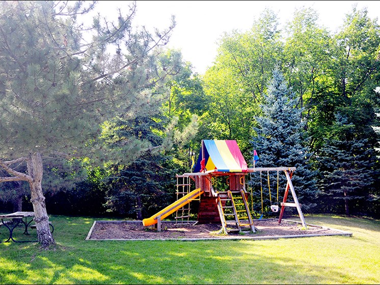 outdoor playground with slide and swing next to a park bench and large trees all around