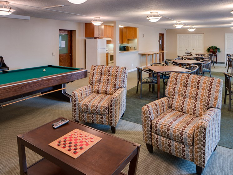 Community room with chairs, tables, board games, and a pool table