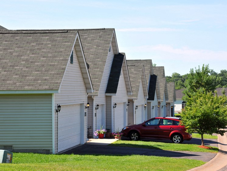 row of houses and garages with a red car parked in front of one