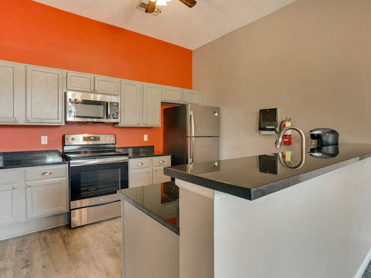 community kitchen with orange wall and stainless steel appliances