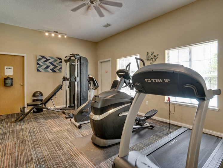 fitness room with treadmill and other equipment