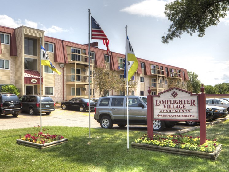 Exterior shot of apartment building with sign that says