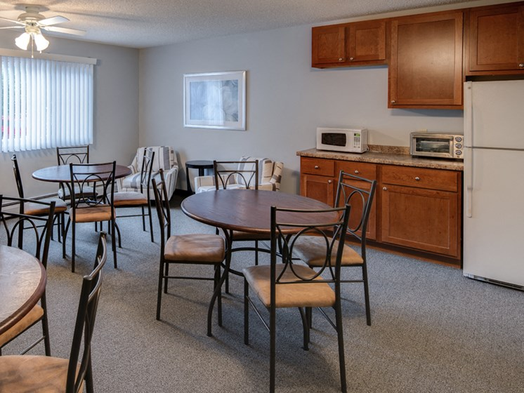Community room with tables and chairs, a refrigerator, microwave, and toaster oven