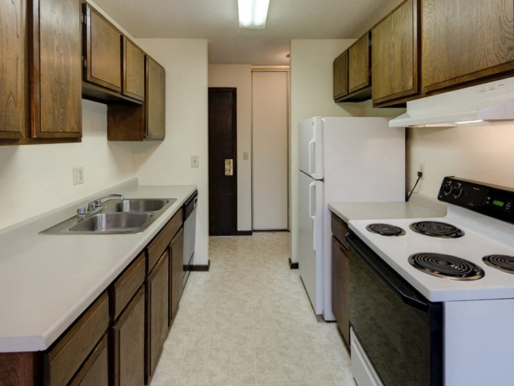 Galley kitchen with sink, stove, and refrigerator, and wooden cabinets
