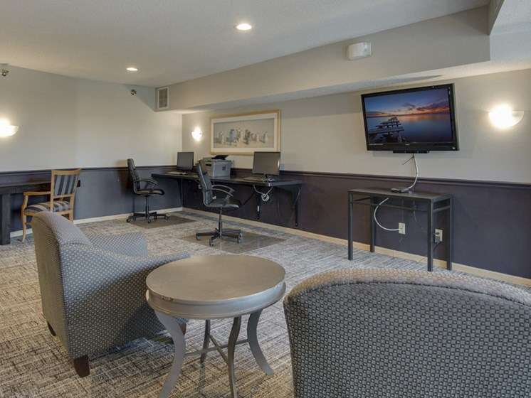 Business center with work stations and chairs facing a wall-mounted TV