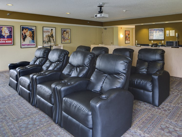 Rows of leather chairs and movie posters on the wall of a theater room