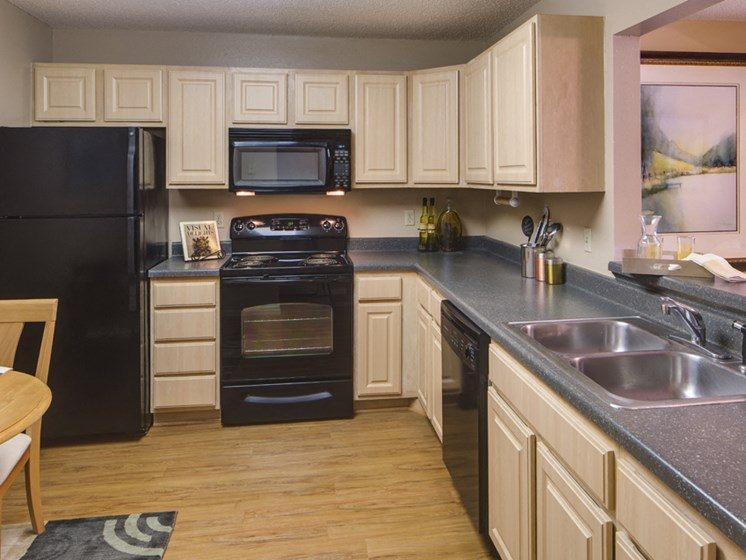 Kitchen with black appliances, wooden cabinets, gray countertops, and hardwood floors