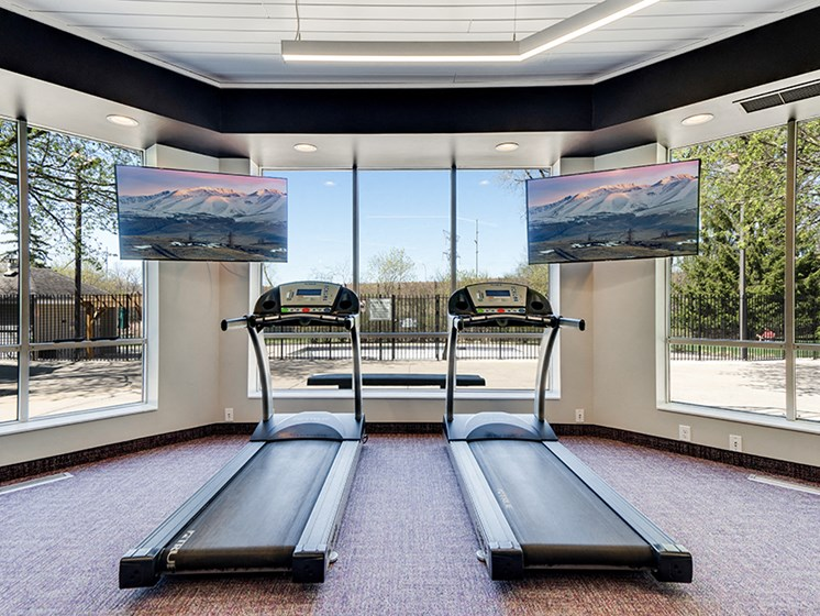 Fitness room with treadmills facing TVs and large windows
