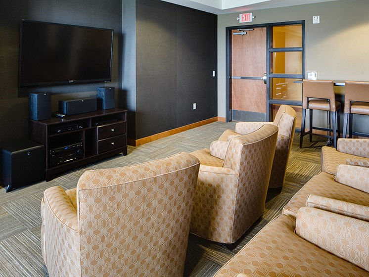 Media room with rows of chairs facing a large TV