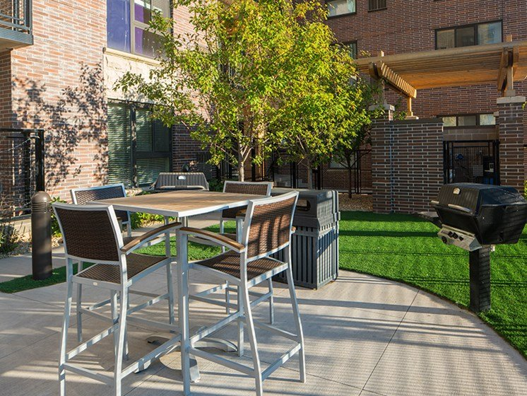 outdoor grilling station with chairs and a table