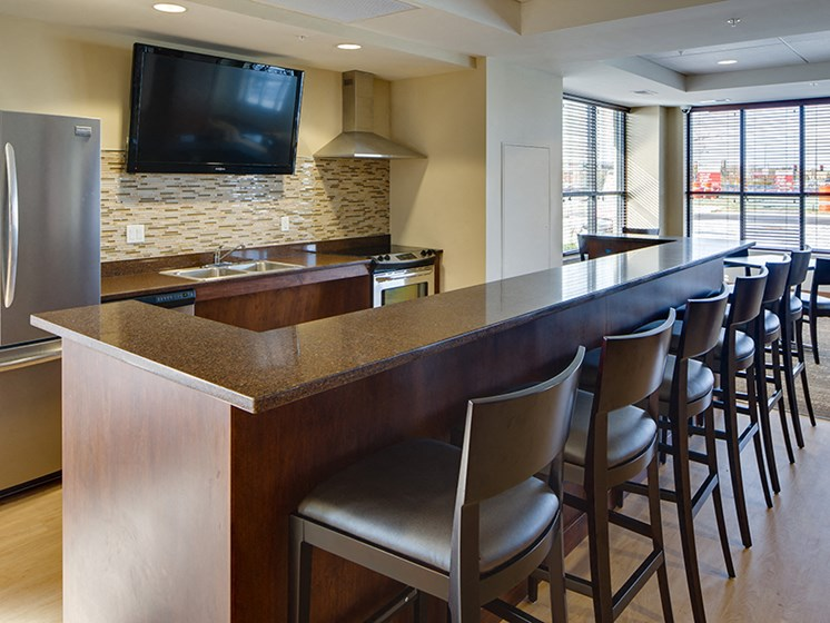 community kitchen with stool seating facing a large TV mounted on the wall