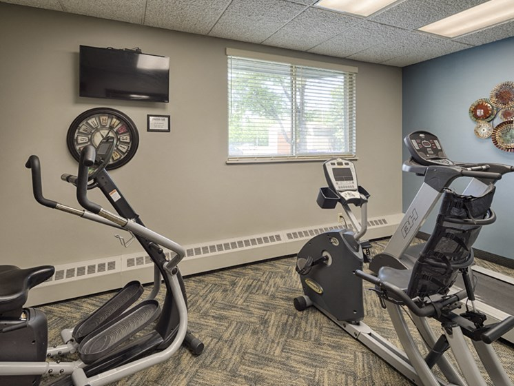 Fitness room with elipticals, treadmil, and a TV mounted on the wall