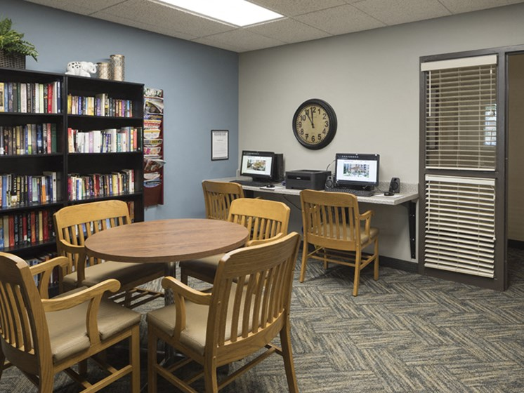 Library with circular table, a stocked bookshelf, and two desktop computers