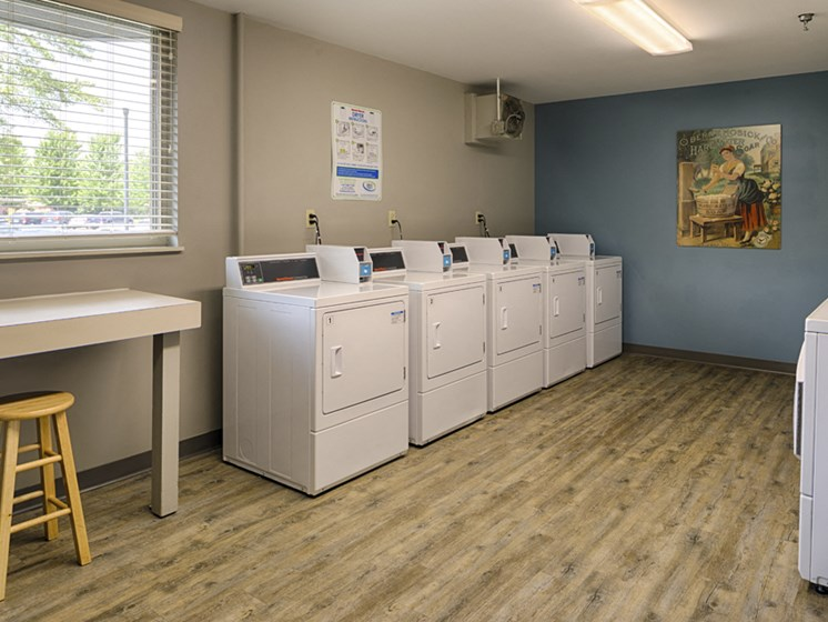 Laundry room with many washing machines and dryers and a folding table