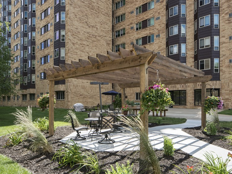 Outdoor sun terrace over patio seating, surrounded by mulch and potted plants