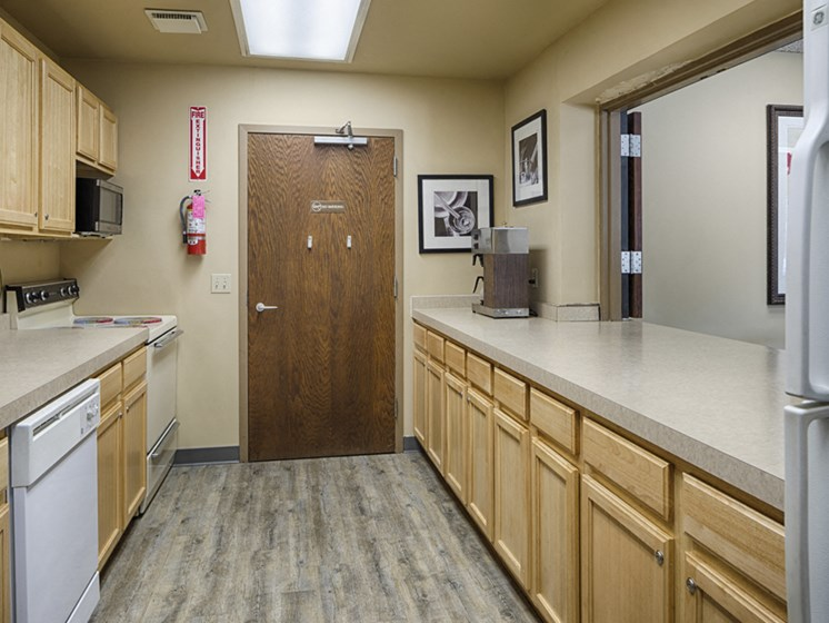 Community kitchen with light wooden cupboards and a galley layout. A stove, oven, and microwave on the left, a refrigerator on the right