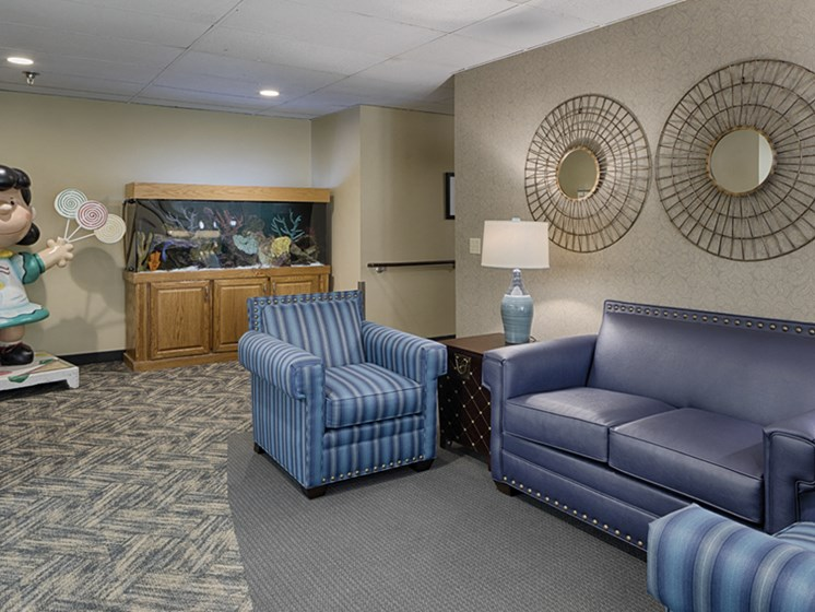 Lobby with a blue sofa and chairs, a fishtank, and a Peanuts