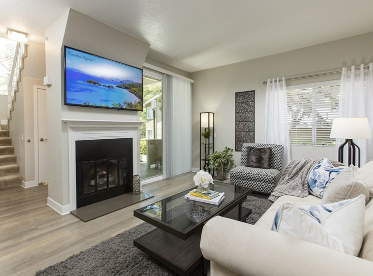 Living area with fireplace, TV,  and sliding glass doors to balcony