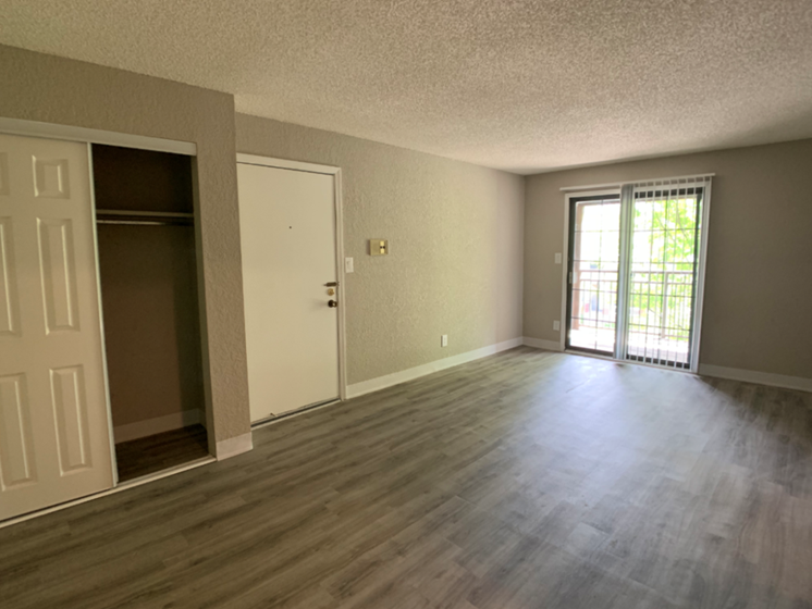 Large living room with vinyl plank flooring and private balcony near the Plaza, Westport, and downtown Kansas City