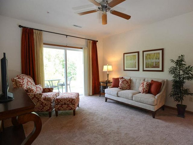 Carpeted Living Rooms With Attached Balconies and Patios at Highlands at Riverwalk Apartments 55+, 10954 N Cedarburg Road