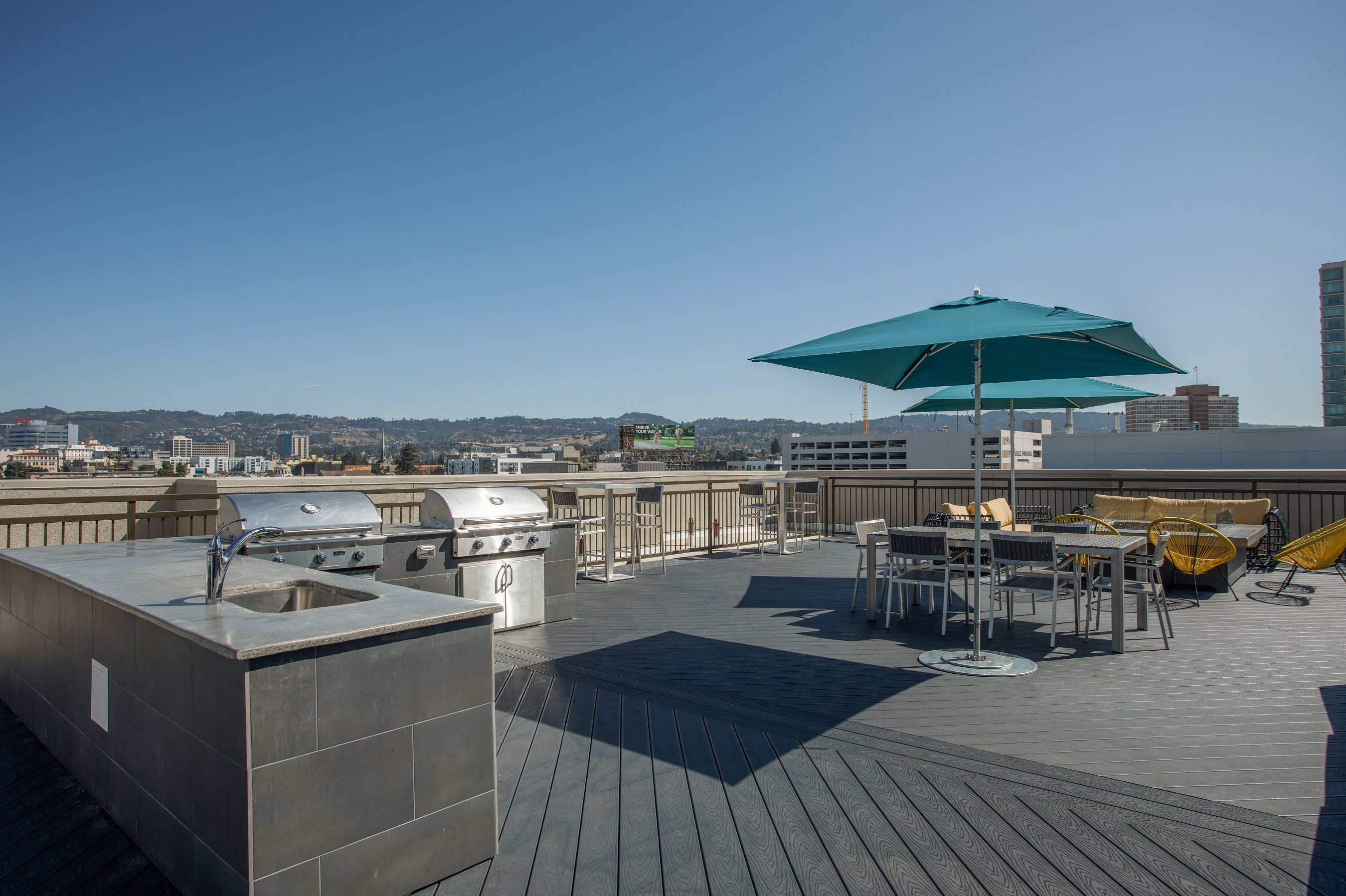 Oakland CA Apartments for Rent - Expansive Rooftop with a Great View of the City Featuring Various Shaded Lounging Areas and Outdoor Grill