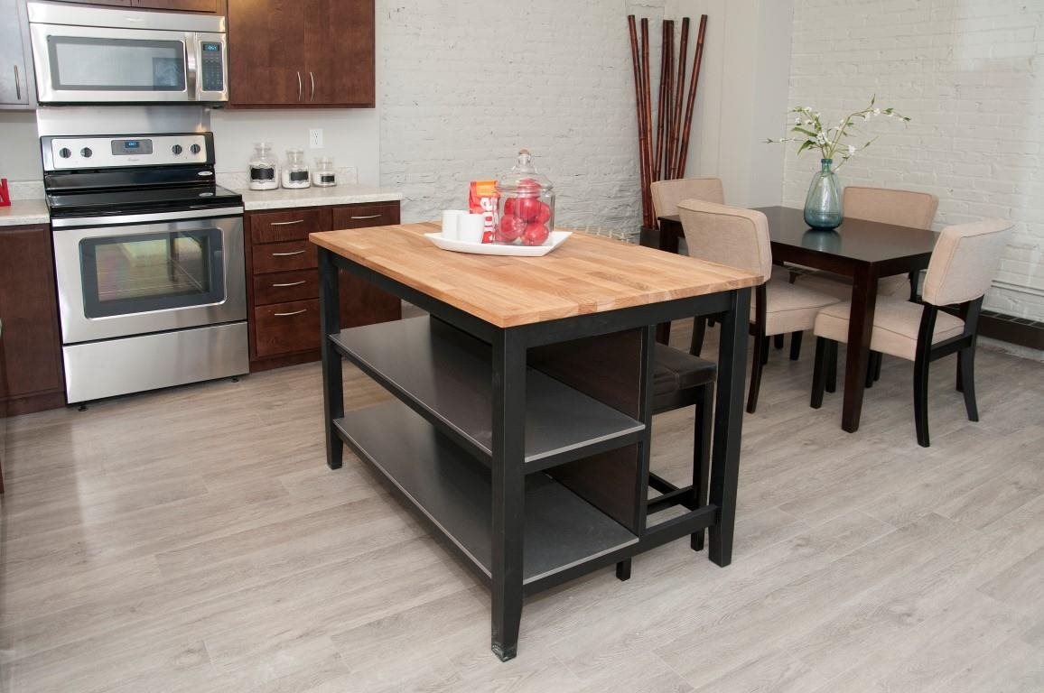 Wooden Counter Top Island with Black Legs in Kitchen of The Cameron