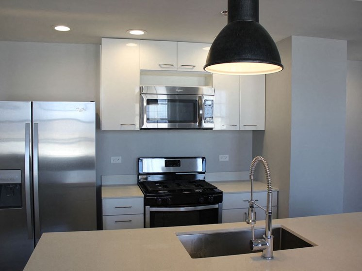 kitchen with modern pendant lighting quartz counters and white cabinets