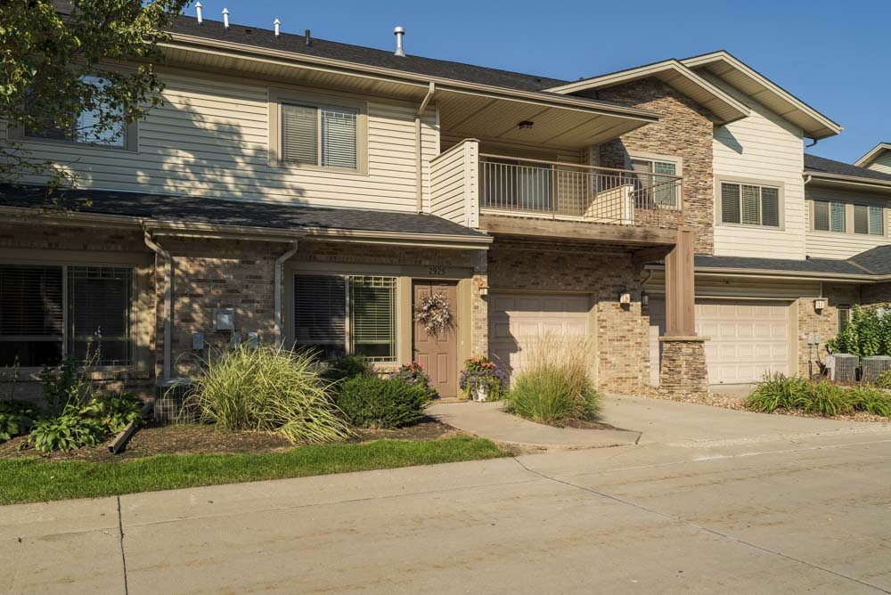 Townhome-style villas with attached garages and large balconies  at Grand Legacy apartments and townhomes in west Omaha NE 68130