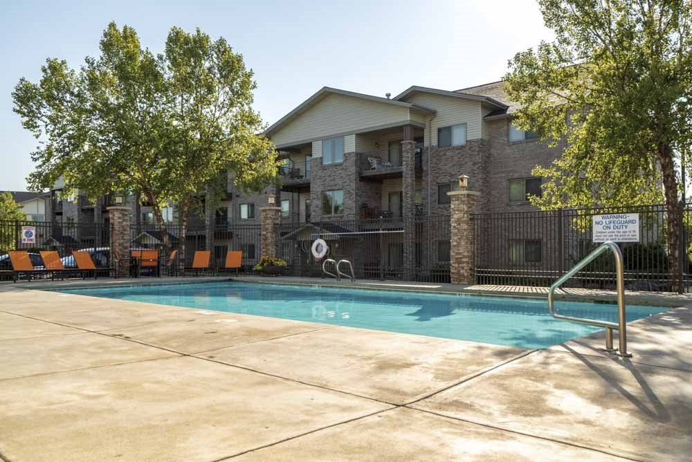 Swimming pool with lounge seating  at Grand Legacy apartments and townhomes in west Omaha NE 68130
