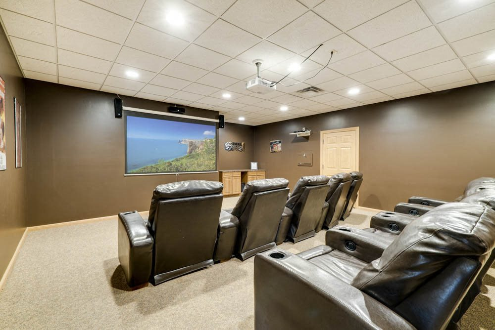 Theater room with comfy chairs and large screen  at Grand Legacy apartments and townhomes in west Omaha NE 68130