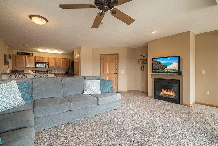 Large and bright living room with a fireplace for extra warmth at Grand Legacy Apartments