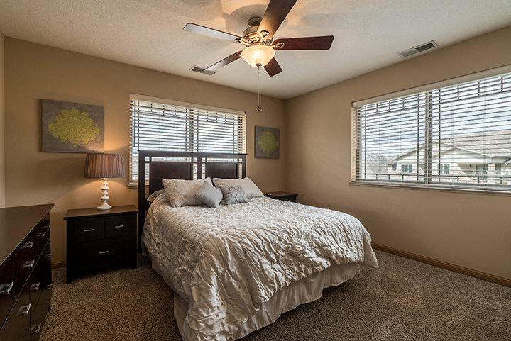 Large bedroom with a ceiling fan and lots of windows providing natural lighting at Grand Legacy Apartments
